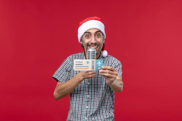 Вид спереди молодой мужчина держит билет и микрофон на красном фоне