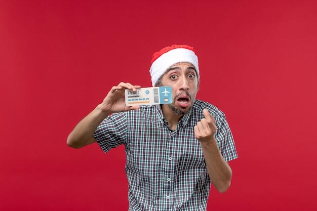 Vista frontale giovane maschio azienda biglietto su sfondo rosso chiaro