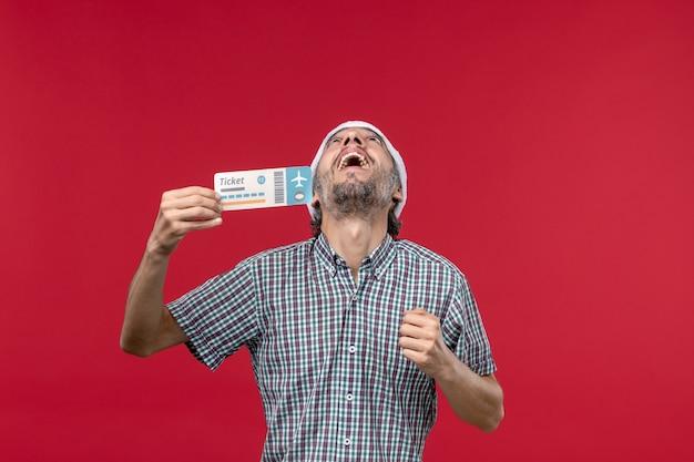 正面図赤の背景にチケットを保持している若い男性