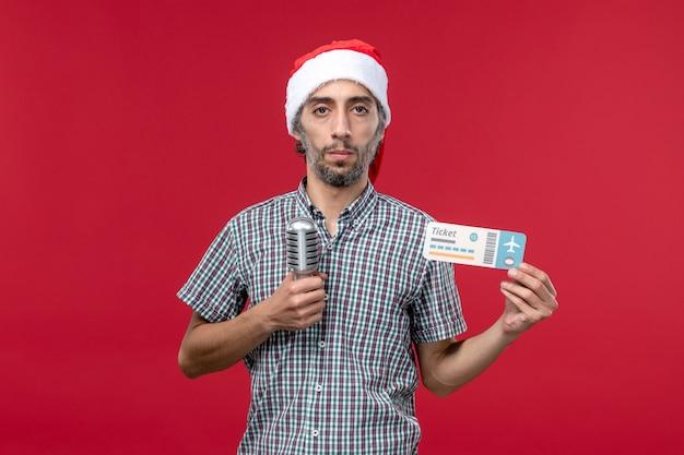 Вид спереди молодой мужчина держит билет с микрофоном на красном фоне