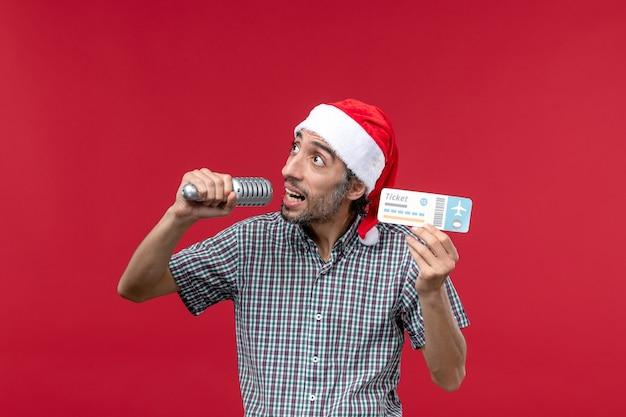 Вид спереди молодой мужчина держит билет с микрофоном на красном столе