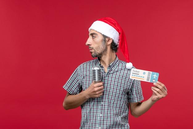 Вид спереди молодой мужчина держит билет с микрофоном на красном этаже музыкальный праздник эмоции