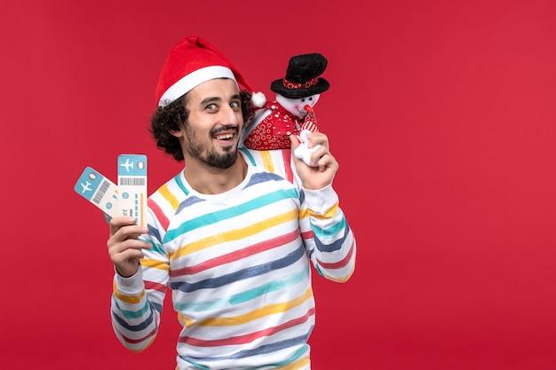 빨간색 벽 남성 빨간색 휴일 새 해에 티켓과 장난감을 들고 전면보기 젊은 남성