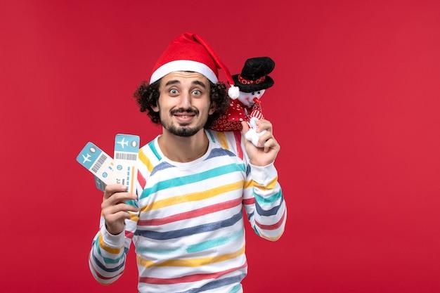 Вид спереди молодой мужчина держит билеты и игрушку на красном столе мужской красный праздник новый год