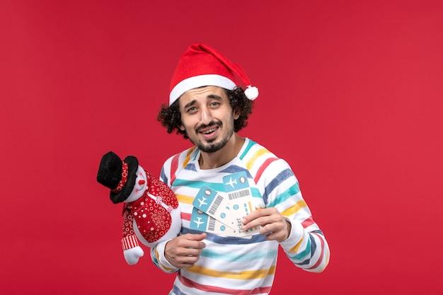 빨간색 벽 남성 빨간색 휴가 새 해에 티켓과 장난감을 들고 전면보기 젊은 남성