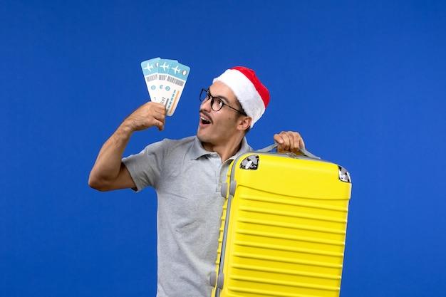 Vista frontale giovane maschio che tiene i biglietti e borsa pesante sull'aereo di vacanza di voli sfondo blu