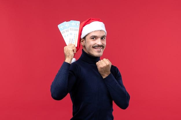 Vista frontale giovane maschio in possesso di biglietti su sfondo rosso