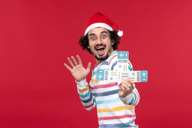 Vista frontale giovane maschio che tiene i biglietti sulle emozioni rosse del nuovo anno di volo aereo della parete rossa