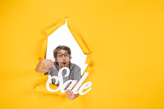 Vista frontale del giovane maschio che tiene la vendita bianca che scrive sul muro giallo chiaro