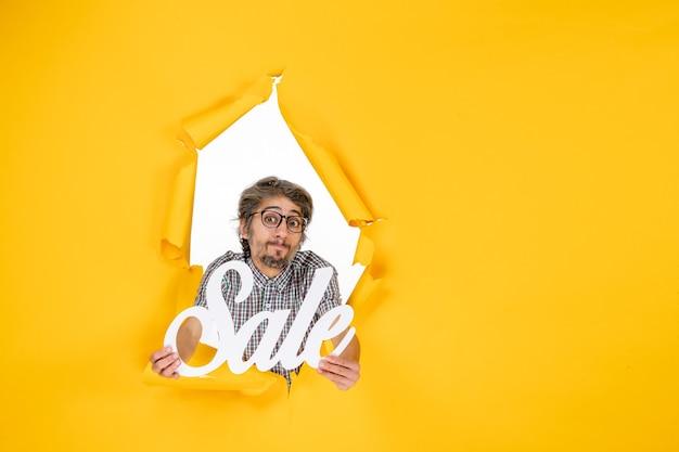 Vista frontale del giovane maschio che tiene la vendita bianca che scrive sulla parete gialla