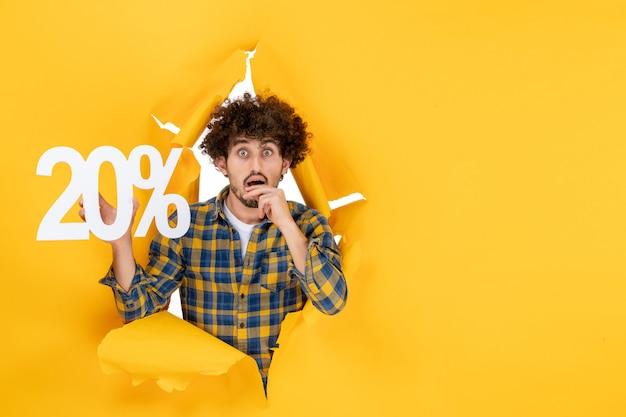 黄色の背景に書き込みを保持している正面図若い男性