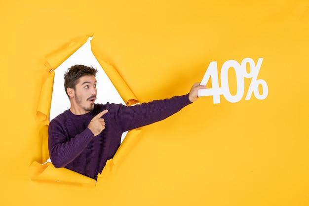 Вид спереди молодой мужчина держит письмо на желтом фоне, делая покупки, рождественский праздничный подарок, цвет фото