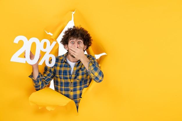 Vista frontale giovane maschio che tiene la scrittura con la faccia scioccata su sfondo giallo