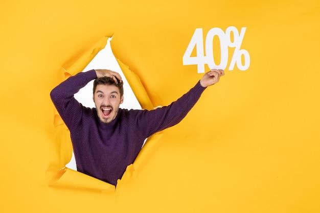 Vista frontale giovane maschio che tiene la scrittura su sfondo giallo colore sfondo natalizio shopping regalo foto
