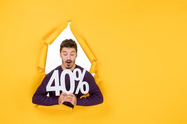 Vista frontale giovane maschio che tiene la scrittura su sfondo giallo colore soldi natale vacanze shopping regali foto