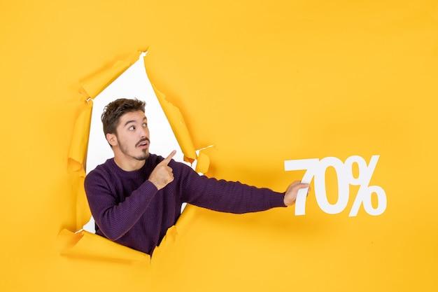 Vista frontale giovane maschio che tiene la scrittura su sfondo giallo foto natale vacanze shopping regalo vendita colore