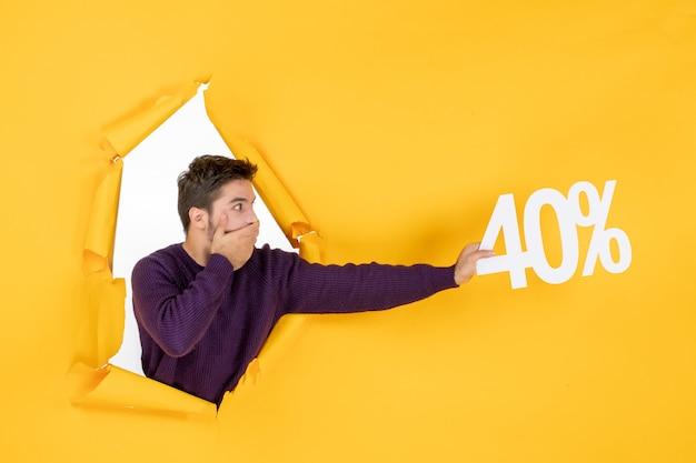 Vista frontale giovane maschio che tiene la scrittura su sfondo giallo shopping natale vacanza regalo foto colore