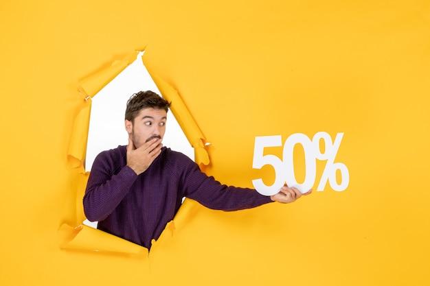 Vista frontale giovane maschio che tiene la scrittura su sfondo giallo shopping vacanze natale colore regalo vendita foto capodanno negozio