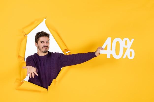 Vista frontale giovane maschio che tiene la scrittura su sfondo giallo shopping regalo di natale foto a colori