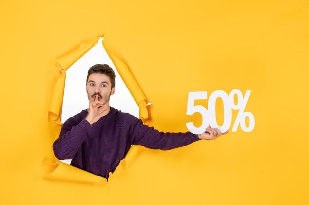 Vista frontale giovane maschio che tiene la scrittura su sfondo giallo shopping regalo di natale vendita foto vacanze