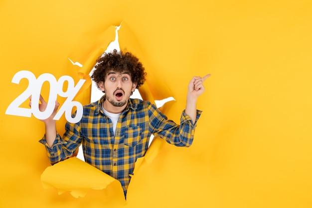 Vista frontale giovane maschio che tiene la scrittura su sfondo giallo