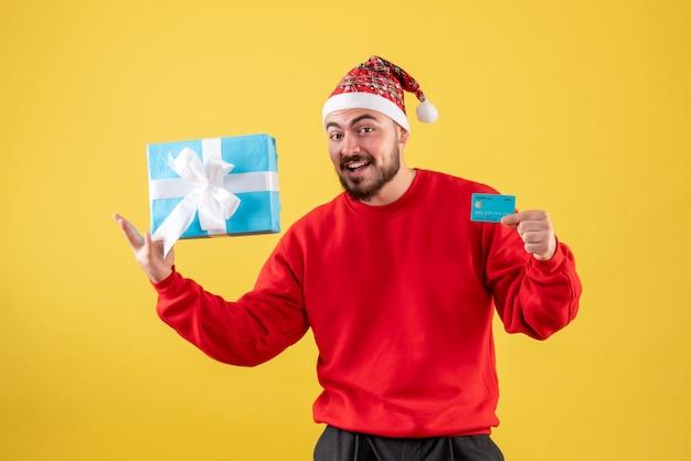 黄色の背景にクリスマスプレゼントと銀行カードを保持している正面図若い男性