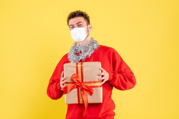 無菌マスクに存在するクリスマスを保持している正面図若い男性