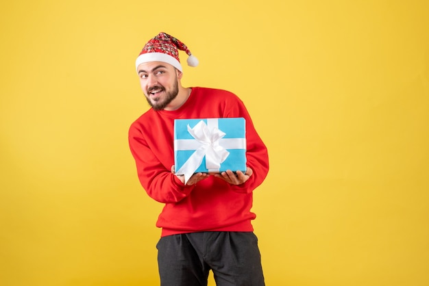 Front view young male holding xmas present on a yellow background