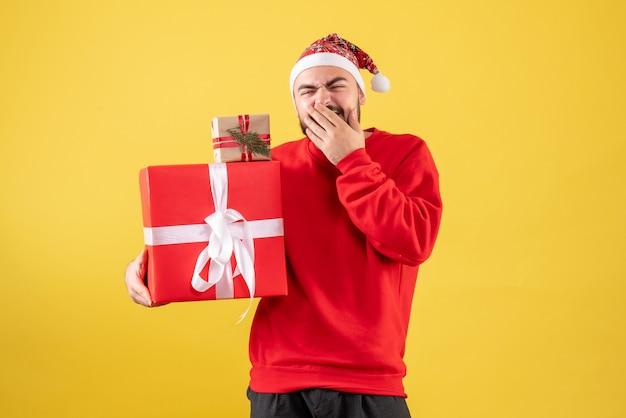 黄色の背景にクリスマスプレゼントを保持している正面図若い男性