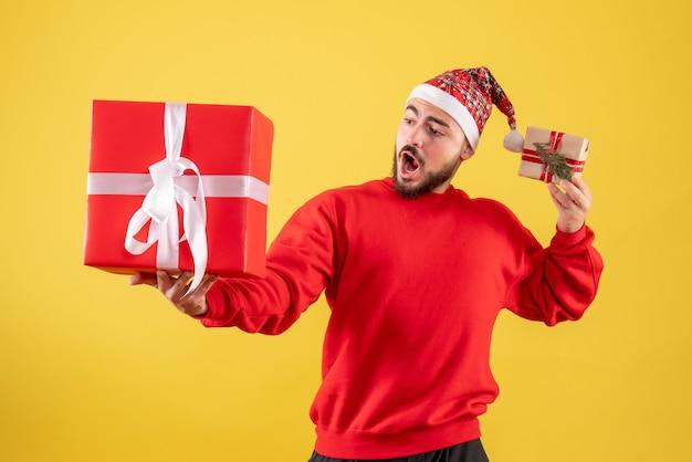 Вид спереди молодой мужчина держит рождественские подарки на желтом фоне Бесплатные Фотографии
