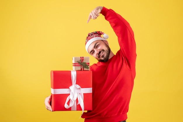 Front view young male holding xmas presents on a yellow background