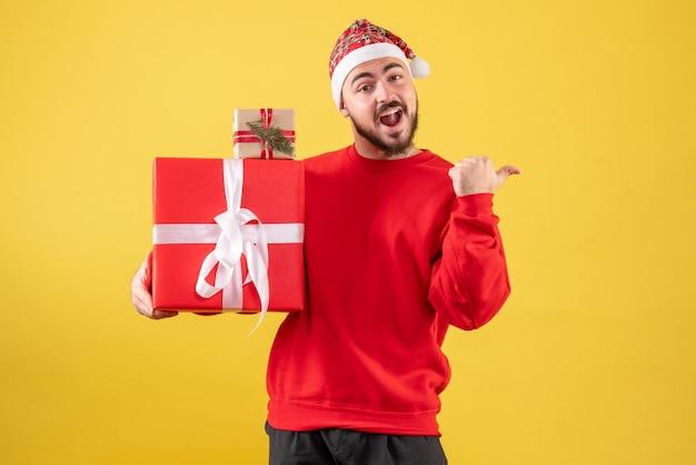 Giovane maschio di vista frontale che tiene i regali di natale su fondo giallo