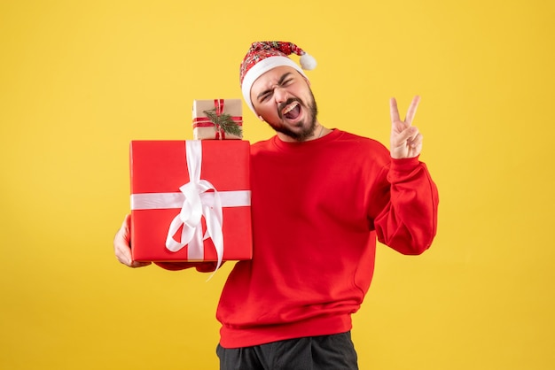 Front view young male holding xmas presents on yellow background