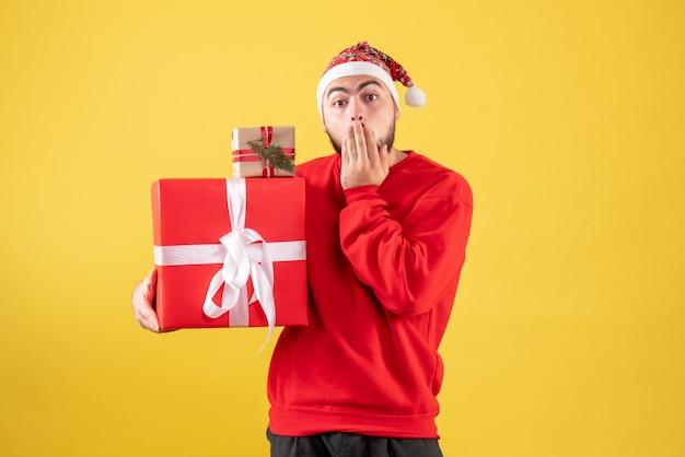 Giovane maschio di vista frontale che tiene i regali di natale su colore giallo