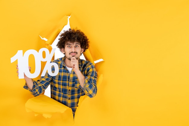 Front view young male holding on yellow background photo sun sale emotion color shirt man shopping