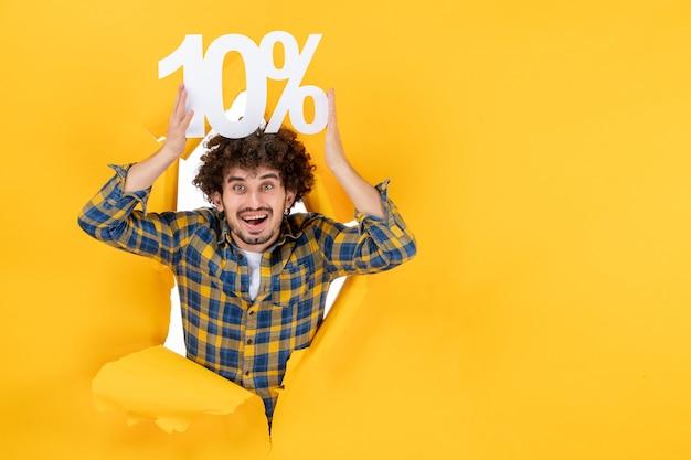 Vista frontale giovane maschio che tiene su sfondo giallo