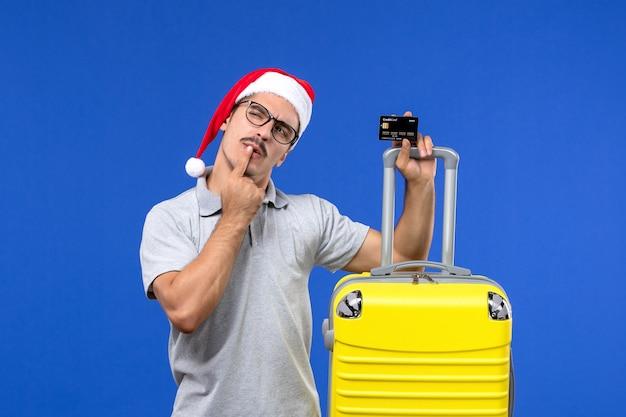 Giovane maschio di vista frontale che tiene la carta di credito del sacchetto giallo su una vacanza di emozione di viaggio del fondo blu