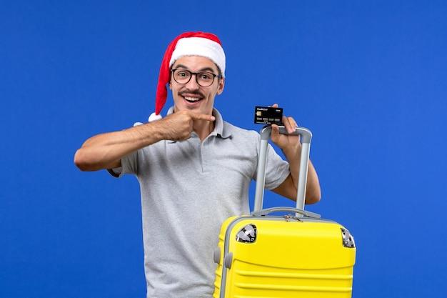 Giovane maschio di vista frontale che tiene la carta di credito del sacchetto giallo su un'emozione di vacanza di viaggio del fondo blu