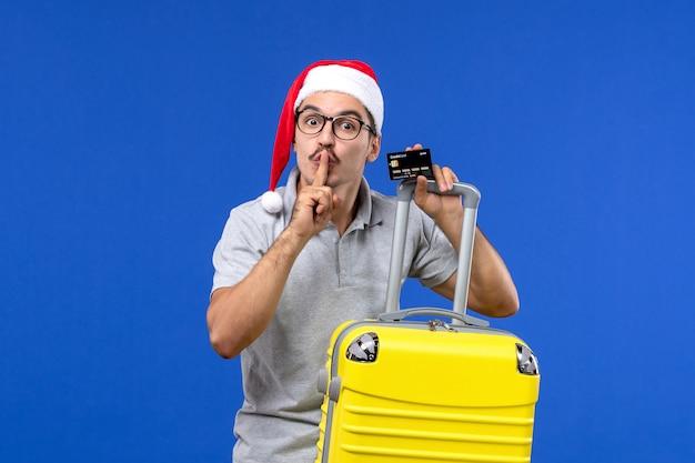 青い机の休暇旅行の感情に黄色のバッグの銀行カードを保持している正面図若い男性