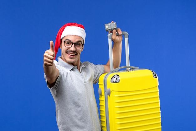 Вид спереди молодого мужчины, держащего желтую сумку с банковской картой на синей стене, поездка в отпуск, эмоции