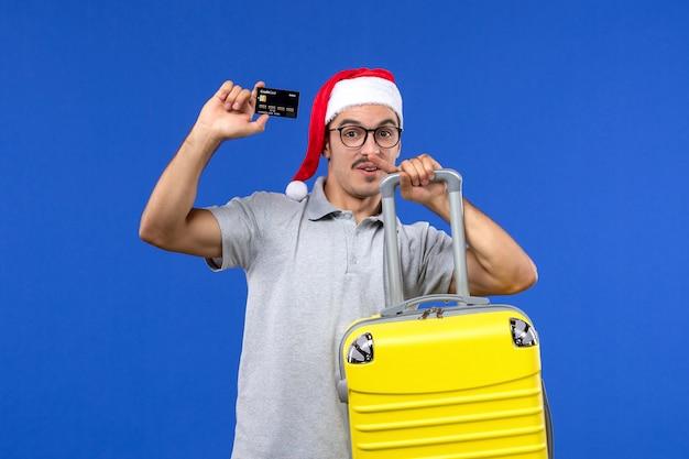 Вид спереди молодой мужчина держит желтую сумку с банковской картой на синей стене в отпуске на самолете