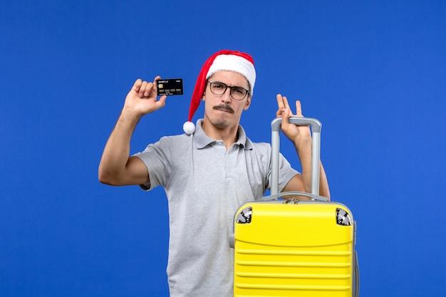 青い壁の休暇の飛行機のフライトで黄色のバッグの銀行カードを保持している正面図若い男性