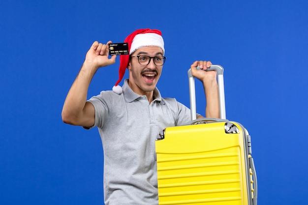 Вид спереди молодого мужчины, держащего желтую сумку с банковской картой на синей стене, полеты самолетов в отпуск