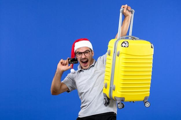 Вид спереди молодой мужчина держит желтую сумку с банковской картой на синей стене, отдых, поездка, эмоция