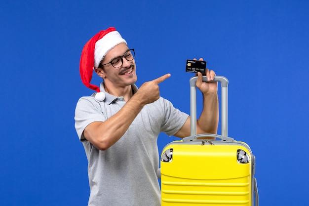 Вид спереди молодого мужчины, держащего желтую сумку с банковской картой на синей стене, поездка, эмоция, отпуск