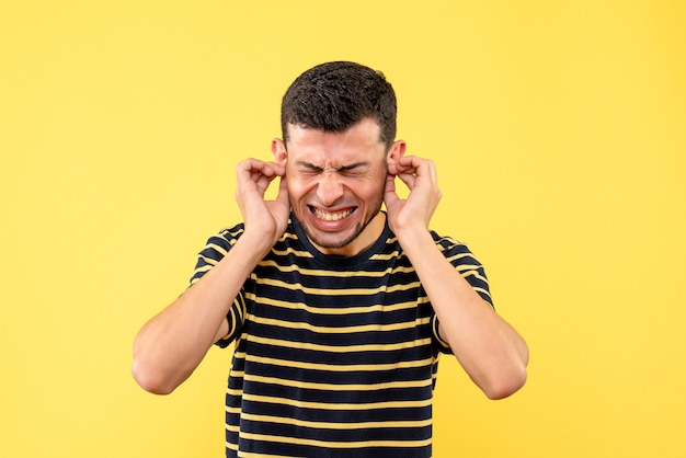 격리 된 노란색 배경에 손으로 그의 귀를 닫는 흑백 줄무늬 티셔츠에 전면보기 젊은 남성