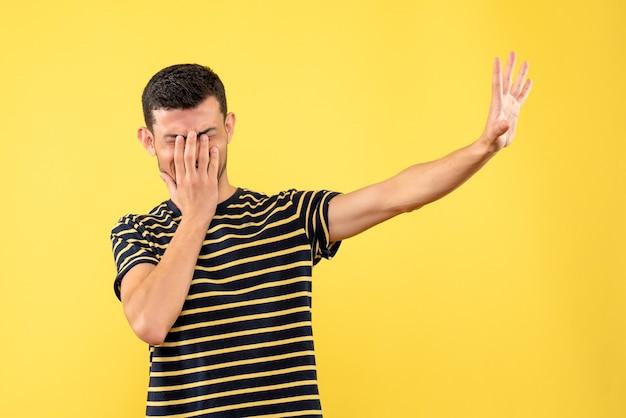 격리 된 노란색 배경에 손으로 얼굴을 덮고 흑백 줄무늬 티셔츠에 전면보기 젊은 남성