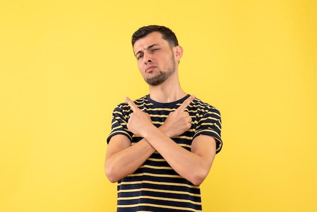 黄色の孤立した背景に手を交差する黒と白の縞模様のtシャツの正面図若い男性