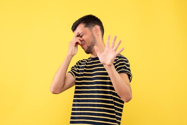 黄色の孤立した背景に頭を保持している黒と白の縞模様のtシャツの正面図若い男性
