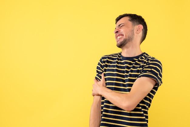 노란색 격리 된 배경에 그의 팔을 들고 흑백 줄무늬 티셔츠에 전면보기 젊은 남성